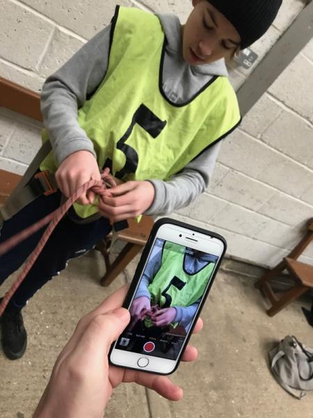 Taking video of tying in to a harness - GCSE PE rock climbing